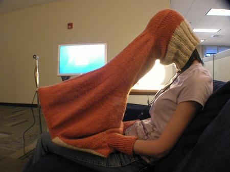 Person mit Laptop-Strickpulli als Blickschutz
